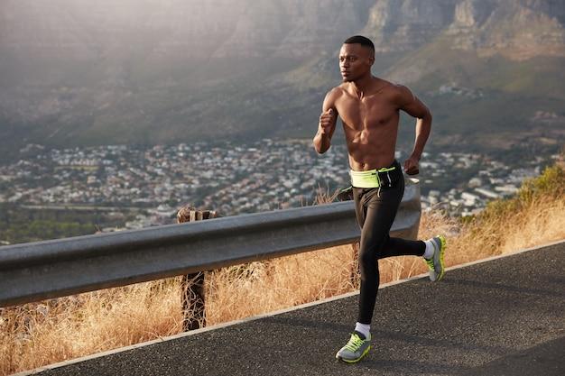 Bez koszuli, ciemnoskóry mężczyzna biegnie szybko drogą, nosi sportowe buty, ma motywację, by wygrywać wyścigi