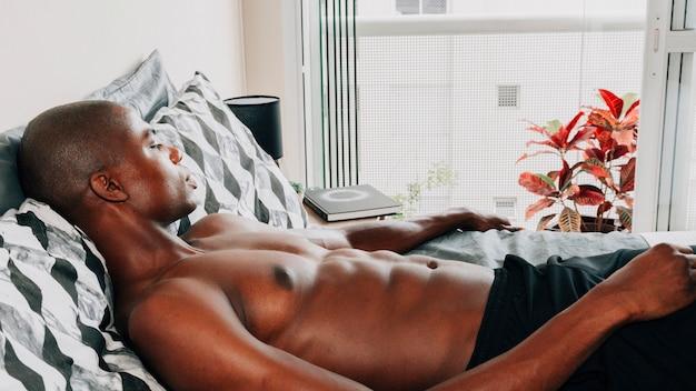 Bez koszuli dysponowany afrykański młody człowiek relaksuje na łóżku