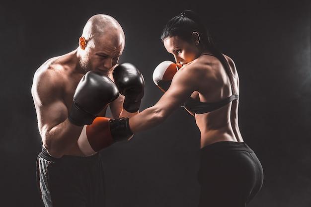 Bez koszuli kobieta ćwiczy z trenerem na lekcji boksu i samoobrony, studio, pali w kosmosie