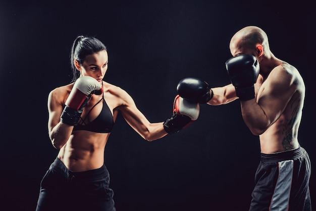 Bez koszuli kobieta ćwiczy z trenerem przy boksem i samoobrony lekcją, studio, ciemny tło. walka kobiet i mężczyzn.