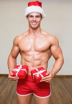 Bez koszuli macho mężczyzna w santa mienia kapeluszowych prezentach