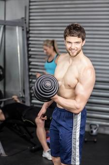 Bez koszuli mężczyzna podnosi dumbbells przy crossfit gym