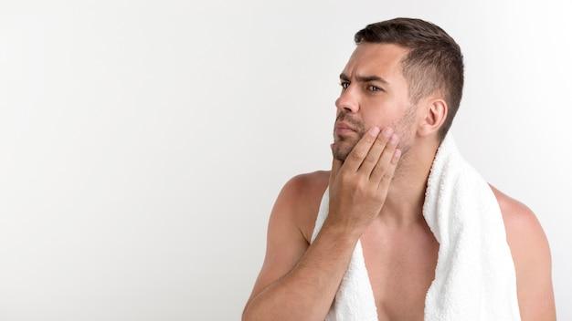 Bez koszuli mężczyzna z ręcznikiem na szyi sprawdza twarzy pozycję przeciw białemu tłu