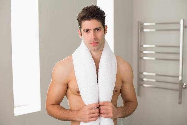 Bez koszuli mężczyzna z ręcznikiem wokoło szyi w domu