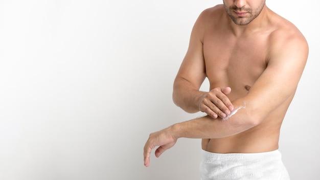 Bez koszuli młody człowiek stosuje śmietankę na ręce przeciw białemu tłu