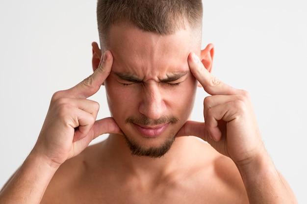 Bez koszuli pozuje z palcami na skroniach z powodu bólu głowy