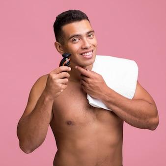 Bez koszuli uśmiechnięty mężczyzna z ręcznikiem za pomocą golarki elektrycznej