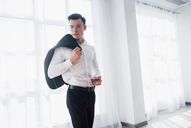 Bez kurtki. luksusowo wyglądający mężczyzna w klasycznym stroju stoi w pokoju i trzyma górę garnituru i szklankę z alkoholem.