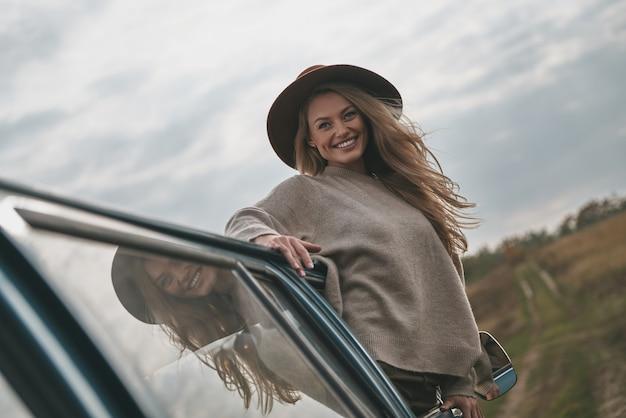 Bez noszenia i bez pośpiechu. atrakcyjna młoda uśmiechnięta kobieta wychylająca się przez okno furgonetki i patrząca w kamerę podczas podróży samochodem