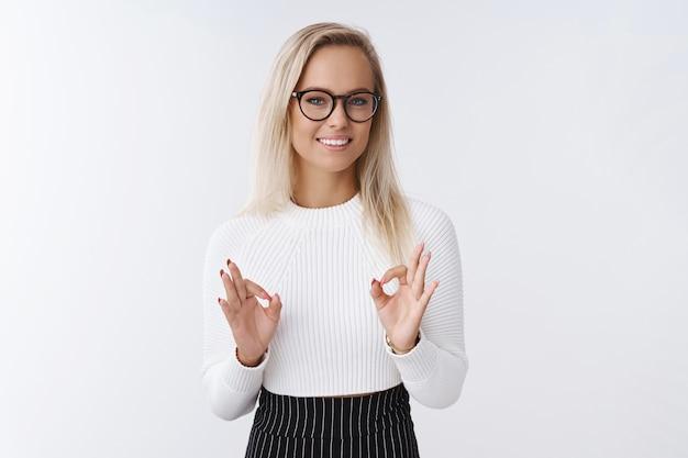 Bez obaw, że sobie z tym poradzę. zrelaksowana, pewna siebie i elegancka blond przedsiębiorczyni w okularach, pokazująca prawidłowe gesty nad ciałem i uśmiechająca się, pozująca chłodno i bez obaw, jak kontrolowanie emocji.