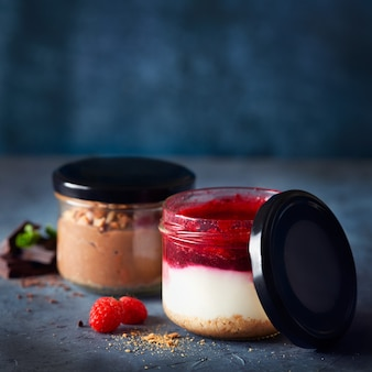 Bez pieczonego sernika z maliną w szklanym słoiku na ciemnoniebieskiej powierzchni zdrowy deser