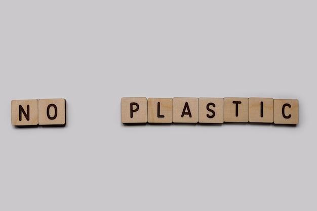 Bez plastiku. napisy drewnianymi literami alfabetu angielskiego na białym tle. widok z góry.