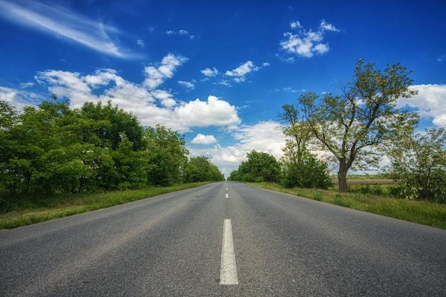 Bez samochodu, pusta asfaltowa wiejska droga, autostrada, w słoneczne lato, wiosenny dzień, oddalająca się w oddali, na tle błękitnego nieba z białymi chmurami i drzewami na poboczu drogi