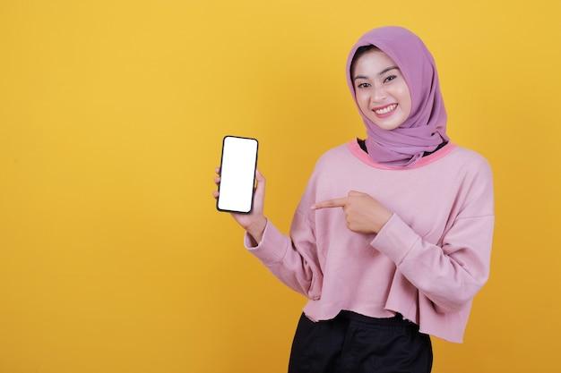 Bez słowa podekscytowana młoda kobieta wskazuje na makietę smartfona, próbuje pokazać coś niesamowitego