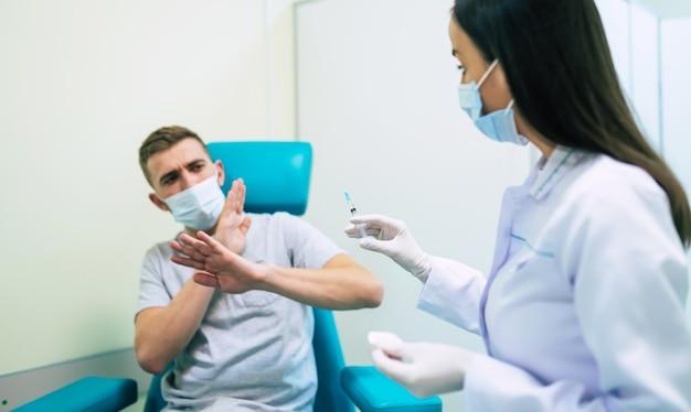 Bez szczepień. przestraszony mężczyzna machający ręką, zatrzymując się, oferując strzykawkę ze szczepionką, odmawiając poddania się szczepieniu.
