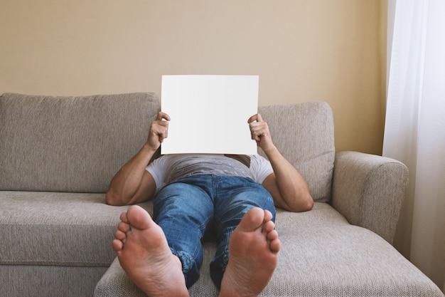 Bez twarzy dorosły mężczyzna leżący na beżowej kanapie z białym pustym miejscem