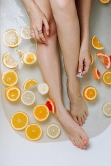 Bez twarzy kobieta trzyma ekologiczną metalową brzytwę w wannie wypełnionej wodą i różnymi pokrojonymi owocami cytrusowymi