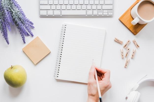 Bez twarzy osoba pisze na notatniku na bielu stole z filiżanką kawy i klawiaturą