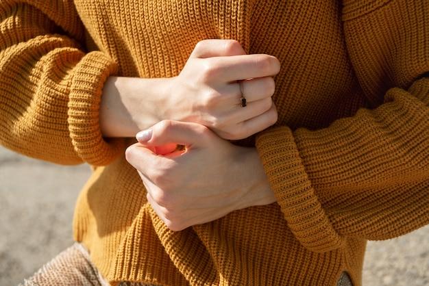 Bez twarzy strzał kobiety w pomarańczowym swetrze, trzymając go rękami na zewnątrz