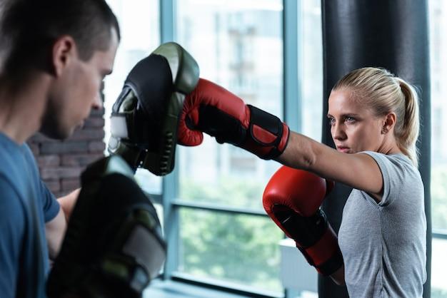 Bez uprzedzeń. niebieskooka piękna kobieta bez uprzedzeń podczas aktywnego boksu z trenerem