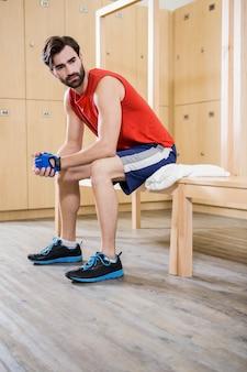 Bez uśmiechu mężczyzna siedzi w szatni na siłowni