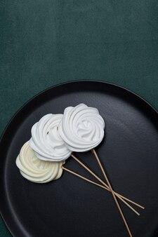 Beza marshmallow na ciemnym talerzu. zephyr na patyku lub oryginalny słodki bukiet na walentynki lub dzień matki.