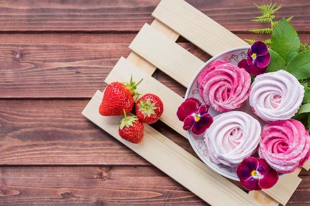Beza zefiru marshmallows na drewnianym tle. hipoteka w mieszkaniu. różowe słodkie domowe ptasie mleczko. kolorowe bezy, świeżo przygotowane pyszne domowe pianki wiśniowe i truskawkowe