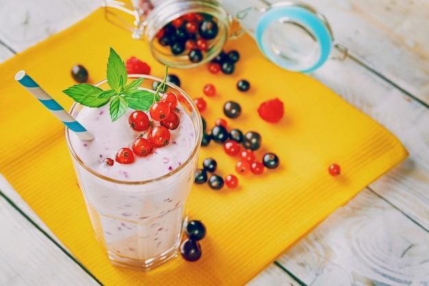 Bezalkoholowe koktajle mleczne ze świeżą porzeczką, maliną i liściem mięty na drewnianym tle, koktajle fitness i żywność, naturalne produkty ekologiczne