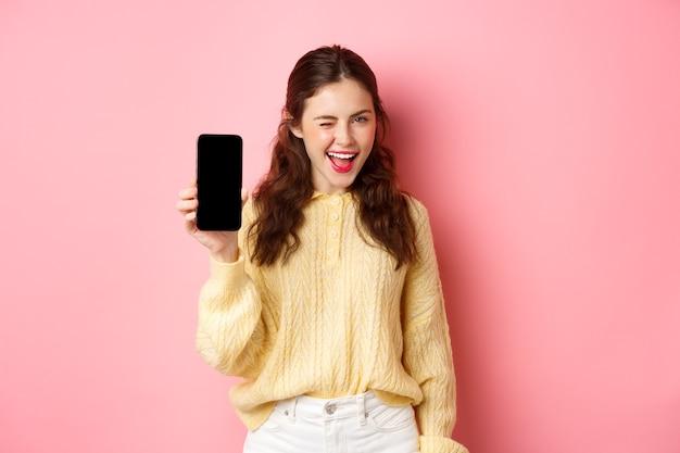 Bezczelna atrakcyjna dziewczyna, pokazująca ekran smartfona, mrugająca i uśmiechnięta, polecająca telefon komórkowy, stojąca przed różową ścianą.