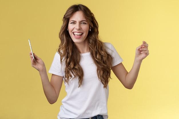 Bezczelna beztroska radosna atrakcyjna kobieta bawiąca się imprezować słuchać fajna nowa piosenka ulubiony artysta taniec podnosić ręce do góry mrużąc oczy bezczelny wygląd aparat wargi synchronizacja trzymać smartfon żółte tło