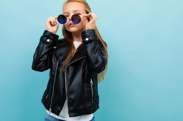 Bezczelna europejska dziewczyna w okularach na jasnoniebieskiej ścianie