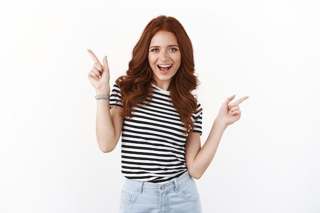 Bezczelna figlarna rudowłosa dziewczyna tańczy optymistycznie, wskazuje na boki, pokazuje promocje od lewej do prawej, uśmiecha się radośnie, zaprasza do wypróbowania oferty, poleca dobre miejsca na reklamę, biała ściana