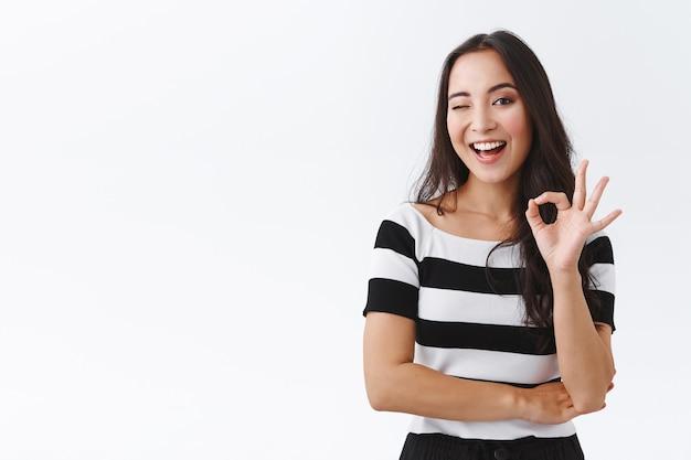 Bezczelna kobieca azjatycka dziewczyna utrzymuje wszystko pod kontrolą, stojąc zrelaksowana i wyluzowana bez zmartwień, pokazując w porządku, potwierdzający lub potwierdzający gest, mrugając i uśmiechając się, białe tło