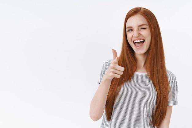 Bezczelna ładna ruda kobieta proste rude włosy bezczelny aparat mrugający do góry gestem zachęcający dziewczynę do świetnej decyzji, jak niesamowity strój, zgadzam się, zatwierdzam fajny plan, biała ściana
