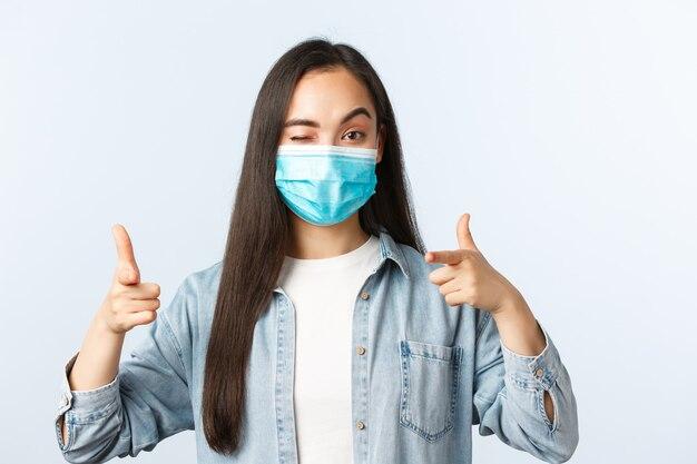 Bezczelna, ładna studentka w masce medycznej mruga i wskazuje na aparat, gratuluje osoby, dobrze się gra
