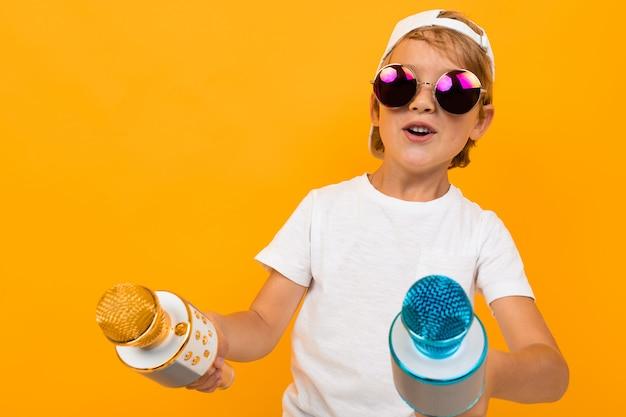 Bezczelny blond chłopiec w okularach trzyma dwa mikrofony na żółtej ścianie