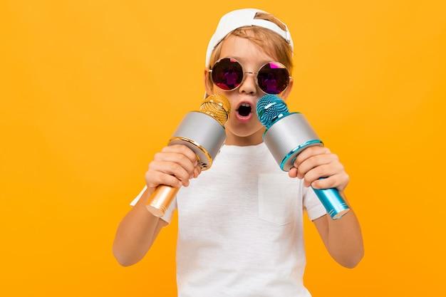 Bezczelny blond chłopiec w okularach z dwoma mikrofonami na pomarańczowej ścianie