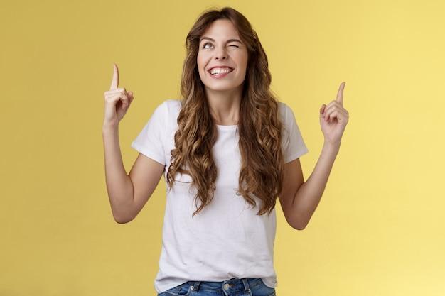 Bezczelny pewny siebie pozytywna atrakcyjna kobieta optymistyczna radosna atmosfera uśmiechanie się ząbkowane mrugnięcie uśmiechem uśmiechanie się bezczelny wskazujący top zawieranie transakcji bóg sugerujący przebiegły nastrój stoisko żółte tło