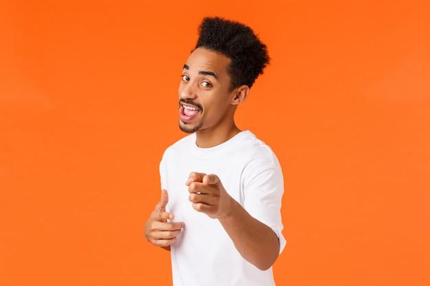 Bezczelny przyjazny przystojny afroamerykański mężczyzna w białej koszulce zachęca do dokonania wyboru lub zakupu, wskazując aparat i uśmiechając się sugeruje wizytę w sklepie, stojący pomarańczowy