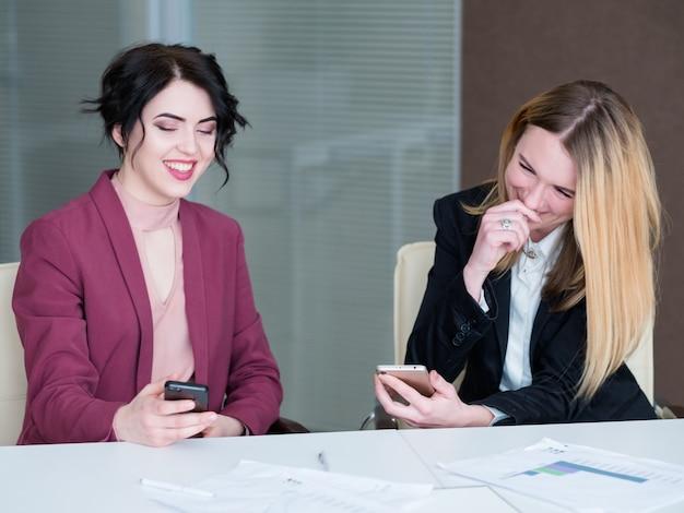 Bezczynni pracownicy patrząc na swoje telefony komórkowe śmieją się.