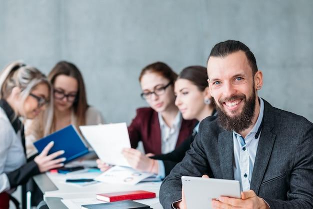 Bezczynny pracownik. członek zespołu leniwy podczas spotkania biznesowego. uśmiechnięty beztroski mężczyzna z tabletem w miejscu pracy.