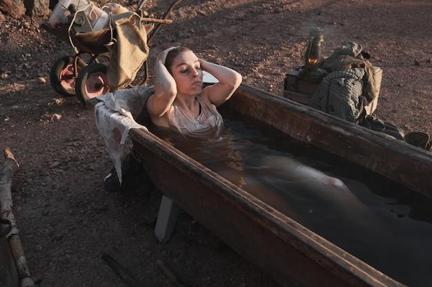 Bezdomna kobieta leżąca w brudnej wodzie i biorąca kąpiel na świeżym powietrzu