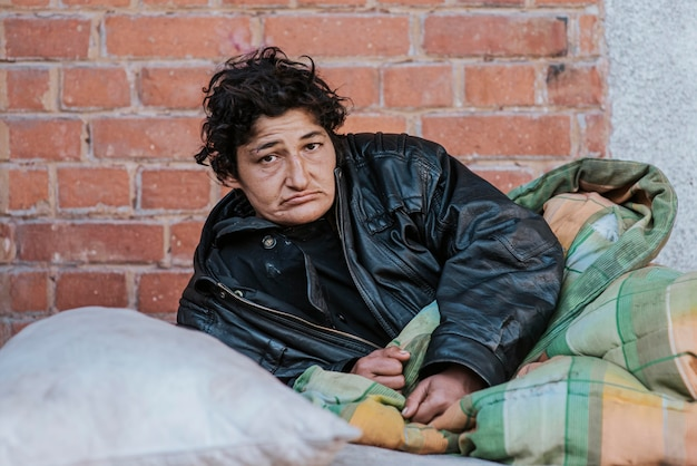 Bezdomna kobieta pod kocem na zewnątrz