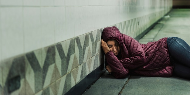 Bezdomna kobieta śpi na podłodze