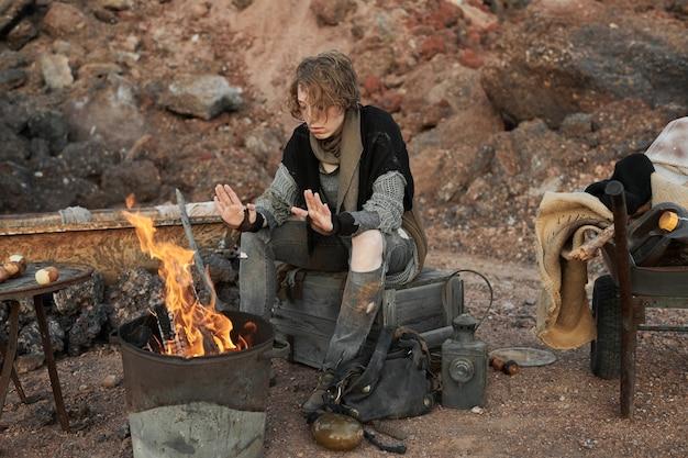 Bezdomna kobieta w podartych ubraniach rozgrzewa się przy ognisku na dworze wśród skał