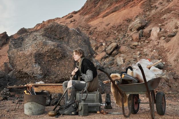 Bezdomna młoda kobieta siedząca przy ogniu rozgrzewająca się lub gotująca posiłek na świeżym powietrzu