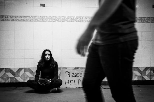 """Bezdomna żebraczka prosząca o darowiznę pieniężną z podpisem """"proszę o pomoc"""""""