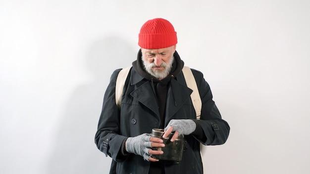 Bezdomny, emeryt, starzec z siwą brodą w płaszczu i czerwonym kapeluszu na białym tle