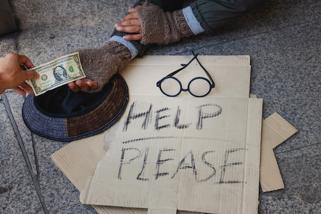 Bezdomny leży na chodniku w mieście. otrzymuje dolara.
