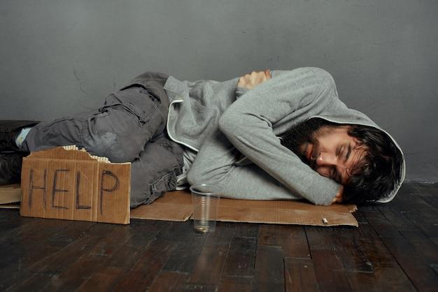 Bezdomny mężczyzna leżący na podłodze ze znakiem pomaga bezdomnym w depresji